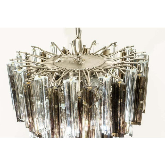 This stylish and chic 1970s Venini Murano glass chandelier will make a definite statement with its clear and smokey topaz...