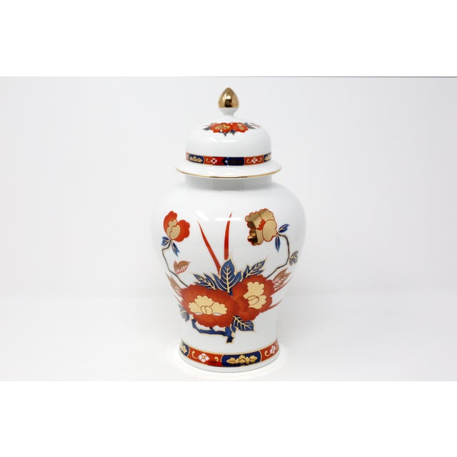 A vintage ceramic Japanese ginger jar, beautifully decorated on both sides with hand-painted flowers in rust, dark blue...