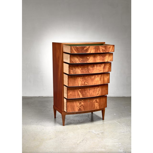 A tall dresser by Frits Henningsen, made of mahogany. The chest holds six drawers, gradient in size and showing a...