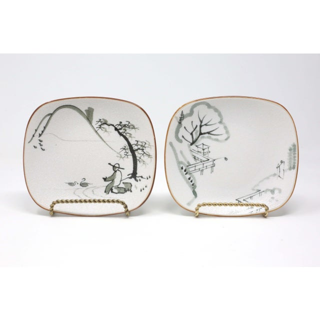 A pair of rounded, footed ceramic trinket, snack or sauce dishes, with hand-painted scenes. Top surface is textured;...