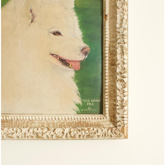 Vintage portrait of a regal, adorable dog (possibly a Samoyed) set against a verdant green backdrop in antique frame. The...