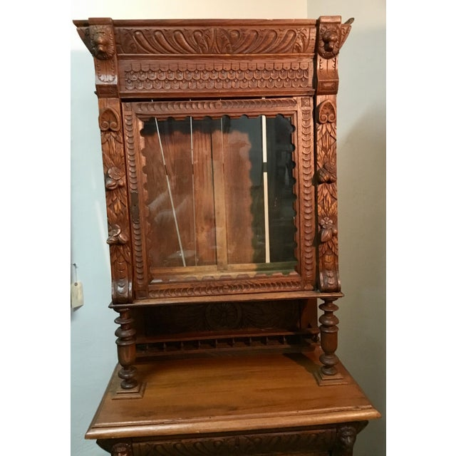 This 19th C. Belgian hunt cabinet has classically carved details featuring lions heads, foliage and flowers. A top cabinet...