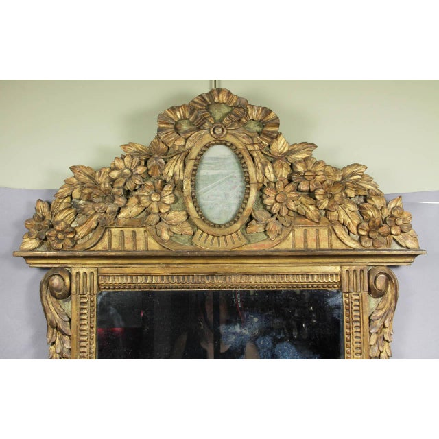 Arched carved crest with floral and leaf carving with central faded watercolor panel over a mirror plate set in a carved...