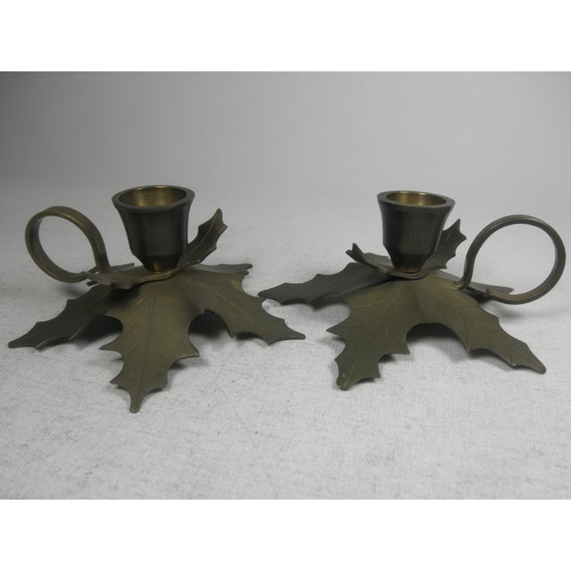 """Haul out the holly..."" with this pair of brass candle holders featuring holly shaped bases. Made by Penco Industries,..."