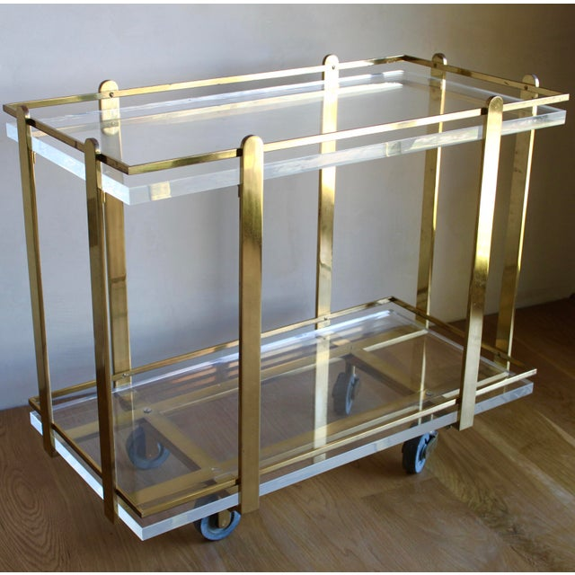 An absolutely incredible and very rare Karl Springer custom, heavy brass bar/serving cart with super thick lucite shelves....