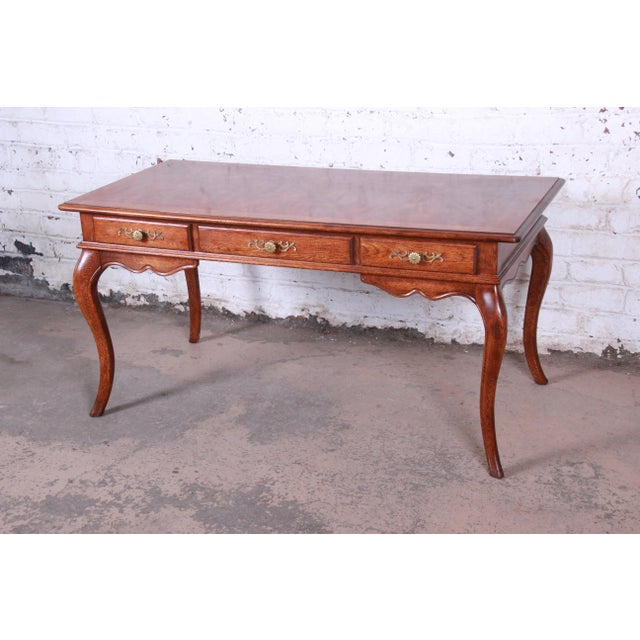 A beautiful vintage French Provincial Louis XV style writing desk by Hickory Manufacturing Co. The desk features nice oak...