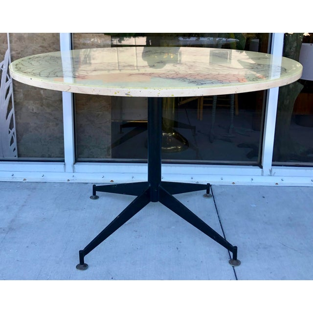 Rare and very chic rItalian ound dining table in the style of Gio Ponti. Black metal base with adjustable brass feet. Top...