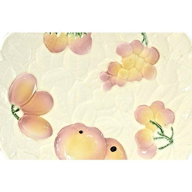 Large vintage French majolica tray with intricate fruit pattern in vibrant pink, yellow, green, and purple on an ivory...