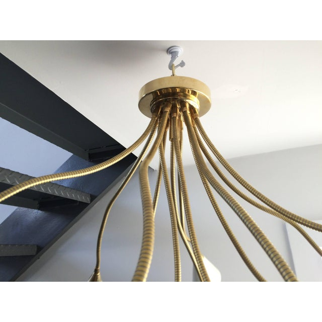 This flush mount brass chandelier has twelve arms or lights with enameled white aluminium reflectors at the ends of the...