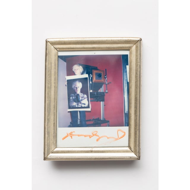 Bill Ray (1936-2020) polaroid photo of Andy Warhol holding a self-polaroid with 20 x 24 polaroid camera in background,...