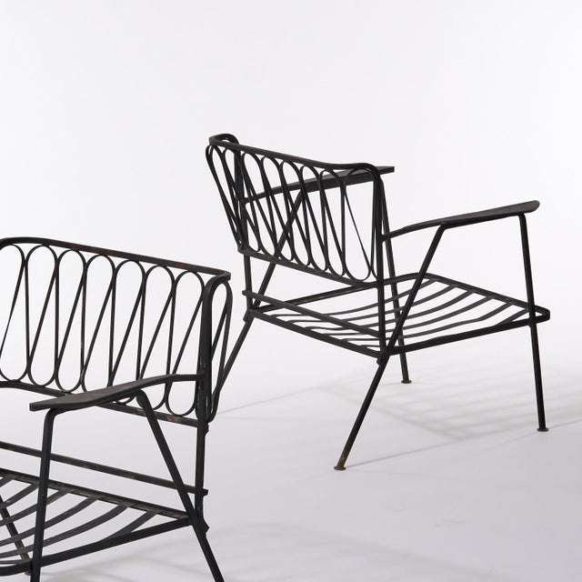 Pair of black wrought iron Ribbon lounge chairs designed by Maurizio Tempestini for Salterini. Cushions not included....
