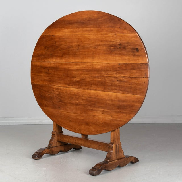 A French wine tasting, or tilt-top table, made of solid cherry wood. Oval top with sturdy trestle base. Legs have nice...