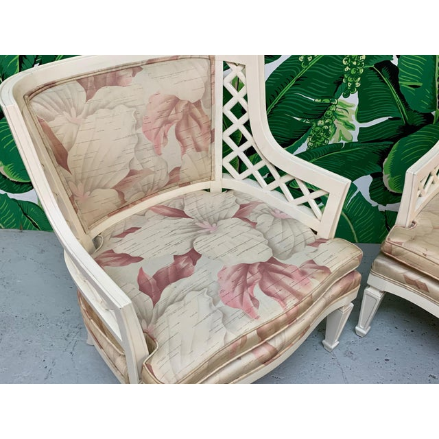 Pair of Hollywood Regency club chairs feature decorative lattice detailing and floral print upholstery. Very good...