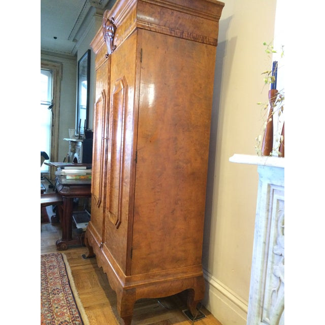 A North European birch wood armoire, in the 17th century style, with a moulded cornice above a central leaf and scroll...