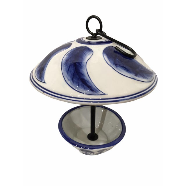 Beautiful porcelain bird feeder with cobalt blue accents. Features a porcelain body attached to a steel rod with a steel...