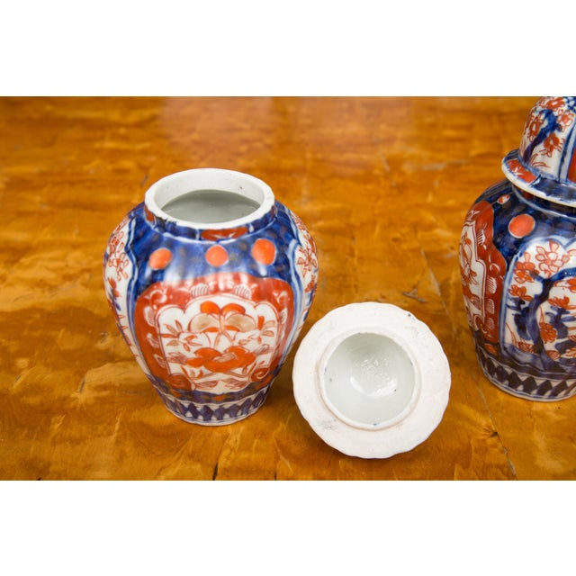 This is a very collectible pair of Classic Imari lidded urns, in traditional colors of cobalt blue and bittersweet orange,...