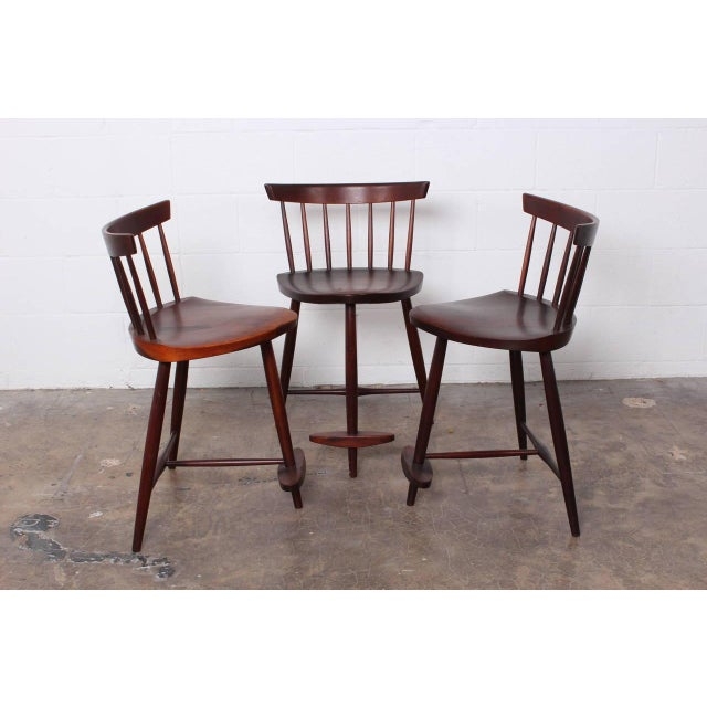 "A set of three walnut ""Mira"" counter height stools by George Nakashima."