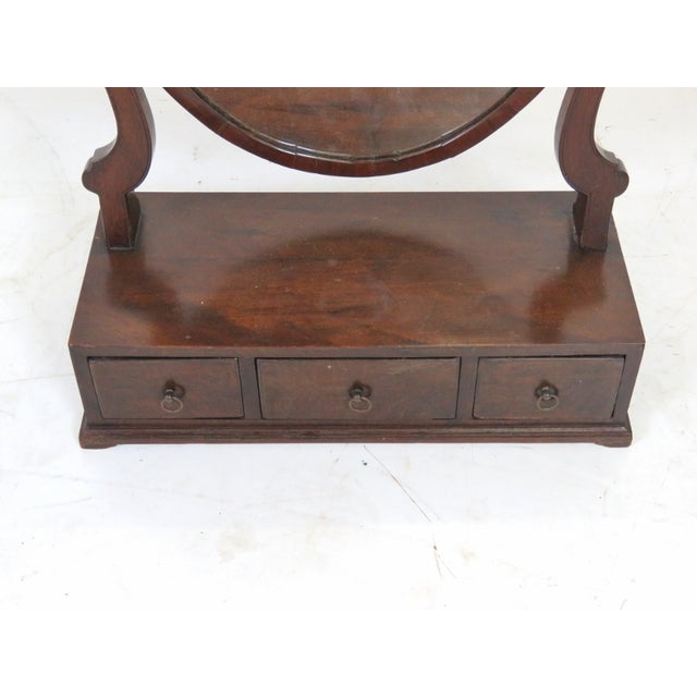 Mahogany with hinged mirror. Features lower shelf with three drawers. Minor damage.