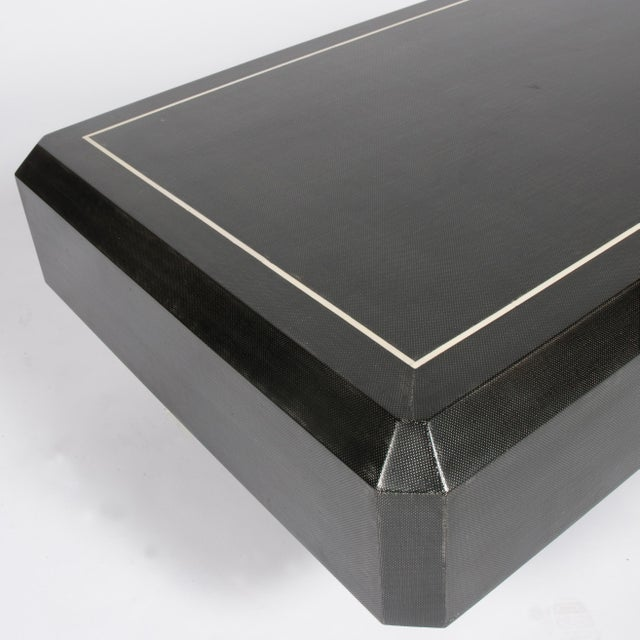 An unusual 1970s Karl Springer coffee table with a faceted, rectangular top covered in lacquered black linen fabric with...