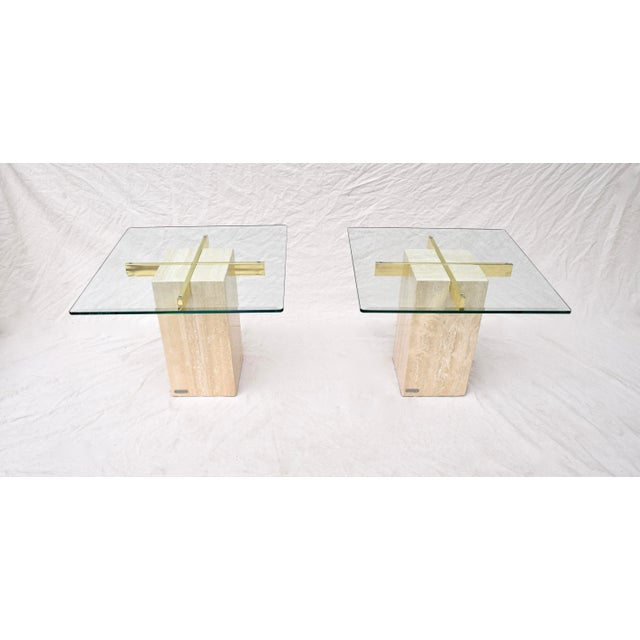 A sculptural pair of tables by Artedi of the United Kingdom. Each table features Travertine marble base, subtly beveled...