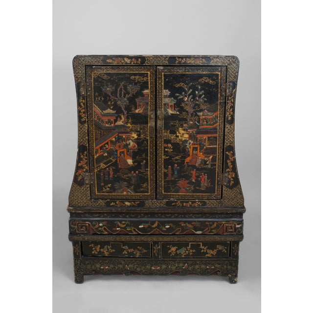 Asian Chinese style (19th Cent) black lacquered and chinoiserie decorated 2 door cabinet with shaped sides and resting on...