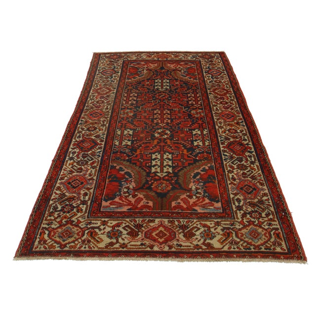 Offered is a Persian Malayer style wool rug. The hand knotted pile features tones of red, tan, and black with geometric...
