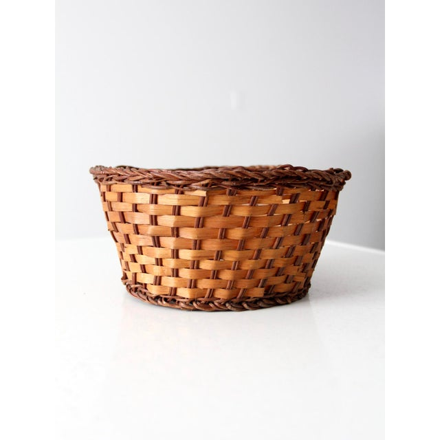 This is a vintage woven basket. The basket features a two tone weave with a tan body and dark brown base and braided rim....