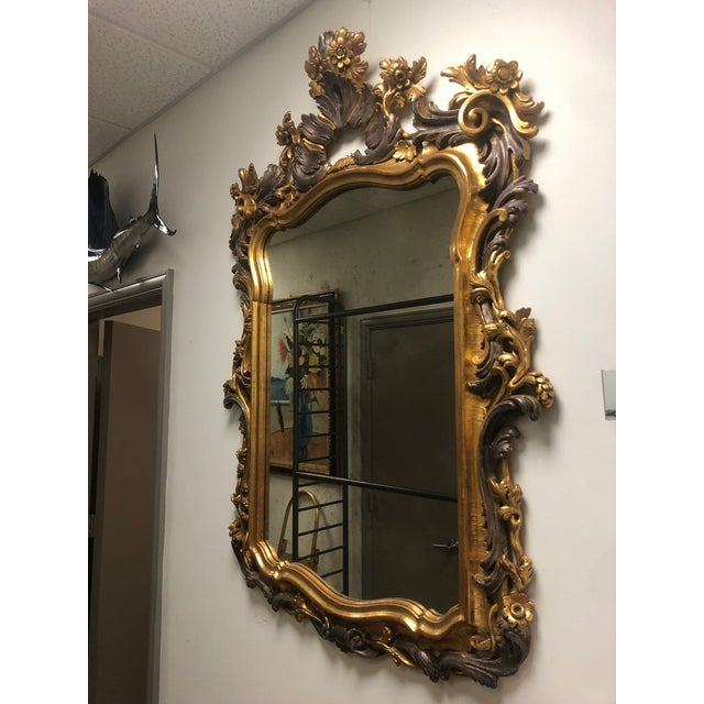 Italian style multitone gold gilt frame mirror. The frame is heavily carved with flower details. Mirror has patina and aging.