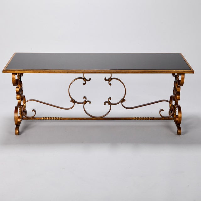 Circa 1930s Italian low cocktail or coffee table with gilded iron base, scrolled feet and black glass table top.