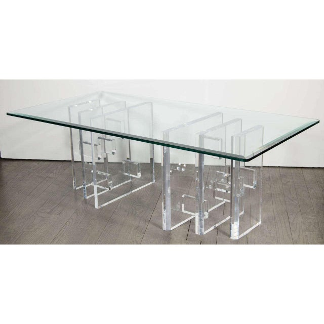 This Mid Century Modern cocktail table features a lucite base composed of multiple lucite forms, creating a wealth of...