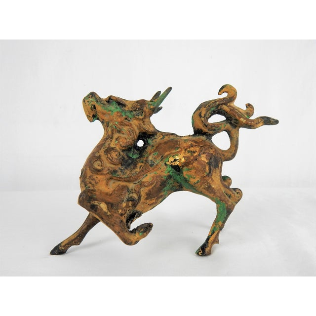 Captivating stylized cast-metal Asian prancing horse figure featuring a rich gilt patina with green oxidation for added...