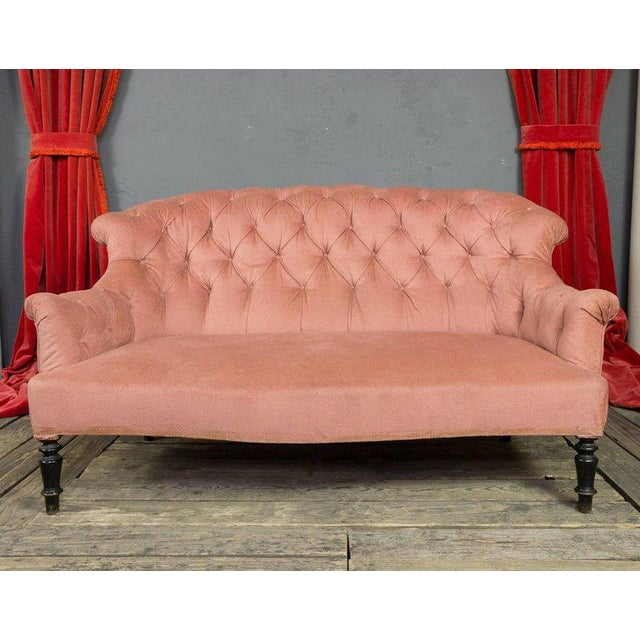 19th century Napoleon III tufted pink settee with scrolled arms and curved back.