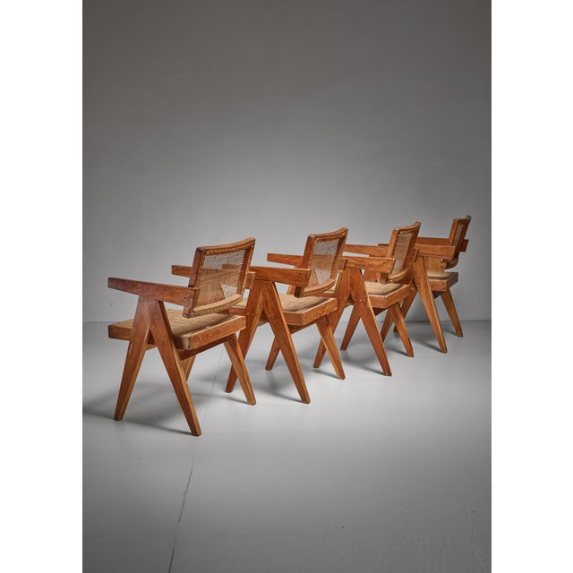 A set of four V-leg chairs from the Chandigarh High Court, by Pierre Jeanneret. The chairs are made of a teak frame with a...