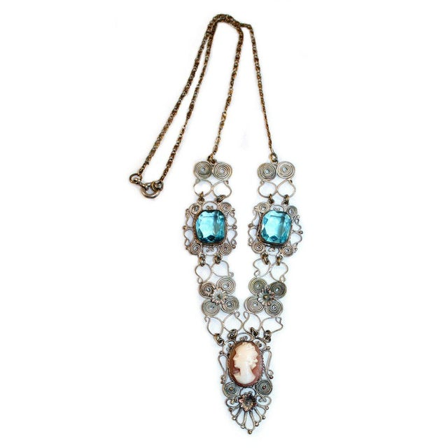 A lovely c1930s silver-plated filigree metal necklace bezel set with a shell cameo and faceted aqua blue glass stones....