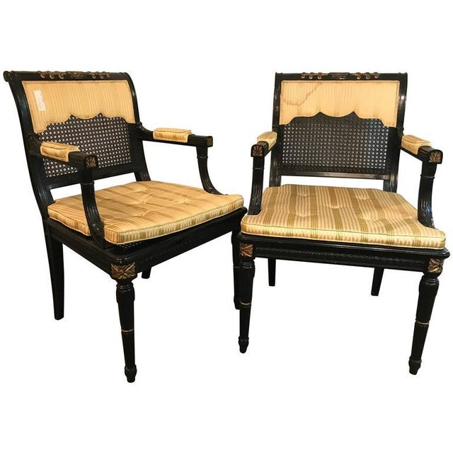Pair of Black and Gold Cane Back Arm Chairs, Fauteuils Attributed Maison Jansen. Each ebonized frame with fine gold...
