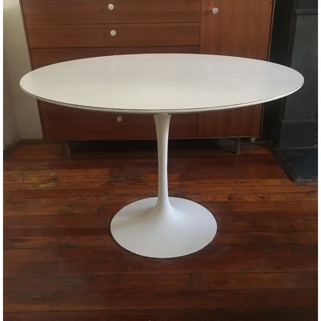 Original Tulip dining table designed by Eero Saarinen for Knoll, enameled cast iron base and white laminate top, retains...