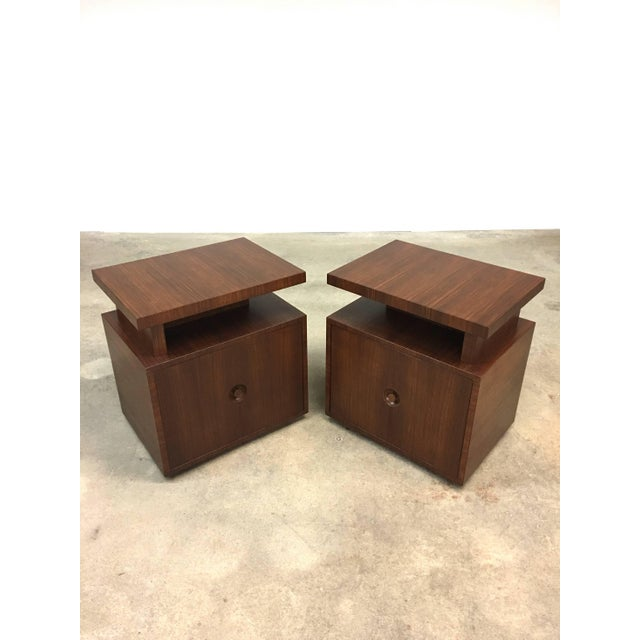 Pair of Andrew Szoeke end tables with floating tops in quarter-sawn rosewood, circa 1948. Single door with recessed,...
