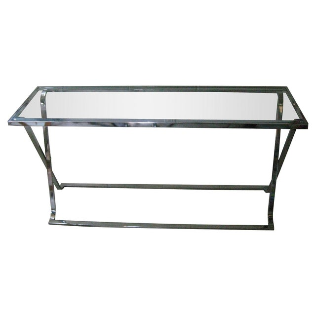 Swanky, minimalist chrome console with X-base, glass insert, and graceful splayed feet. Minor surface tarnish, some wear...