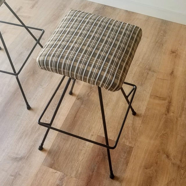 A pair of Mid-Century Modern counter height stools that have been newly upholstered. The stools feature a foot rail that...