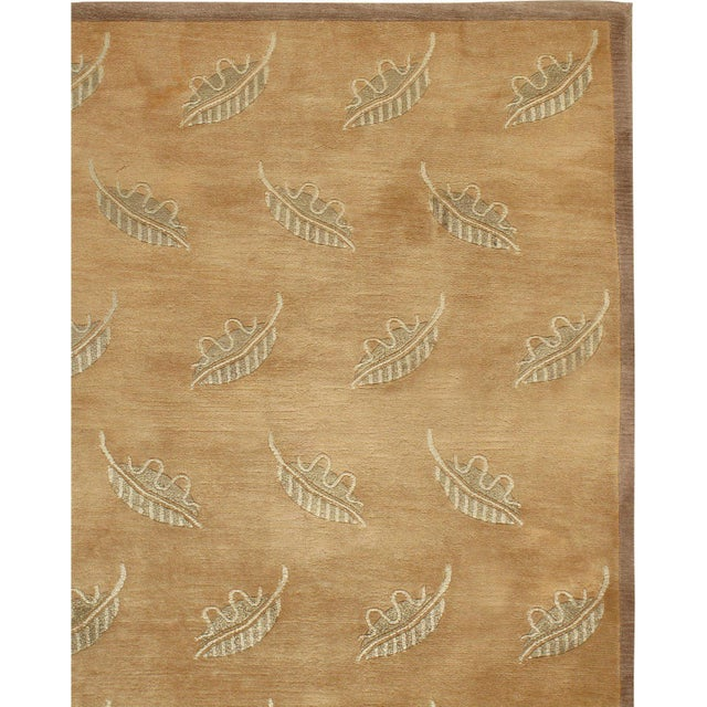 This is a lovely hand knotted modern rug in browns with touches of olive and gold and a leaf design motif.