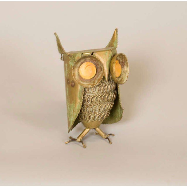 A whimsical hand-forged patinated brass owl with a spiral motif chest and bakelite shaped eyes.