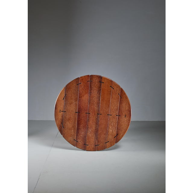 A large and round studio crafted coffee table in palmwood, from Australia The table has a steel frame and the wood parts...