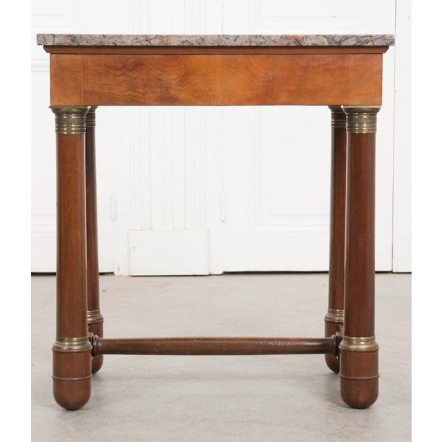 An Empirically styled mahogany side or occasional table, with exceptional marble top, from 1930's France. The multicolored...