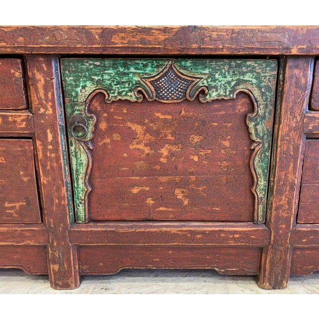 Tibetan dowry chest with decorative overlay and wings. The chest has double drawers on either end and open storage in the...