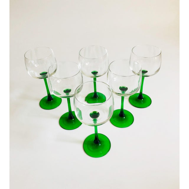 An elegant of set of 6 Mid Century glasses with green stems. Larger sized for wine than the smaller more common champagne...