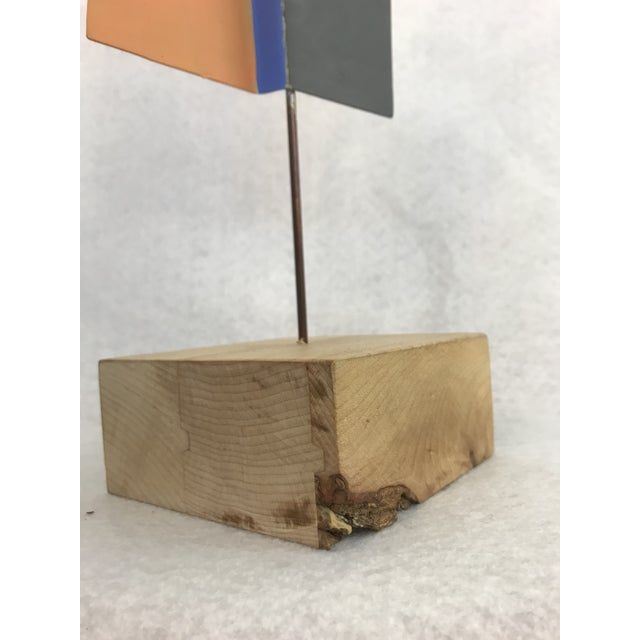 This is a postmodern geometric metal sculpture with a wooden base. The metal is painted with four colors: orange, blue,...