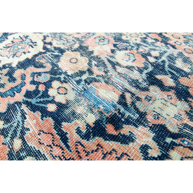 A large-sized, distressed Mahal pile rug with a geometric design on a backdrop of colors such as pinkish salmon for the...