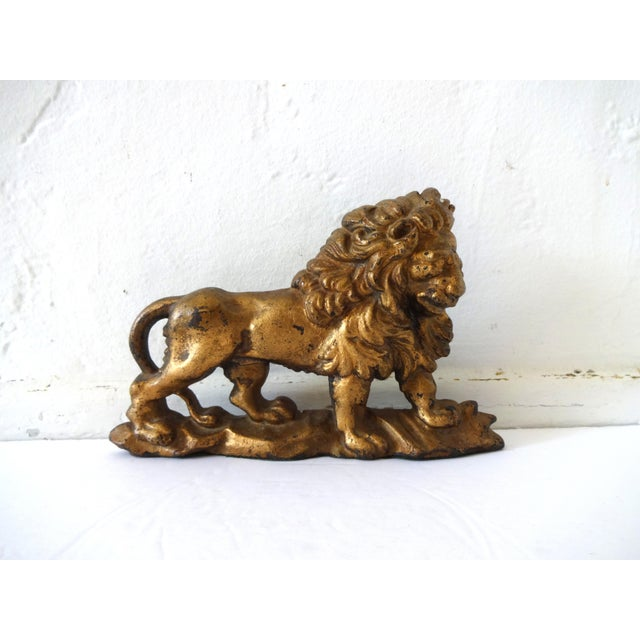 """An antique cast-iron doorstop in the form of a lion, painted in a deep bronze gilt. 19th-Century. 9 1/4"""" wide by 6"""" tall."""