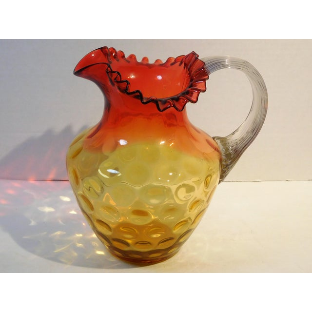 This colorful pitcher has a ruffled tricorn rim flaring over a bulbous body that has optic-coin circles and bubble...