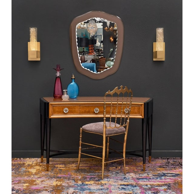 Italian console/vanity with an elegant, curved shape. This piece features a tinted glass top original to the piece and...
